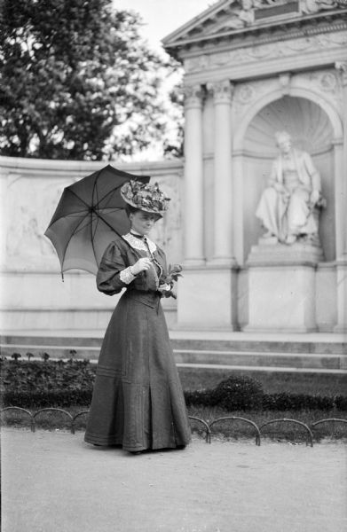 Mary E. Smith standing in front of the Grillparzer monument in the Volksgarten in Vienna, Austria. She is holding a rose in her left hand and an umbrella over her right shoulder.