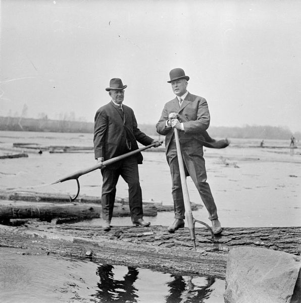 Two businessmen visiting a log drive along the Wisconsin River.  They stand atop a log holding peavey hooks.