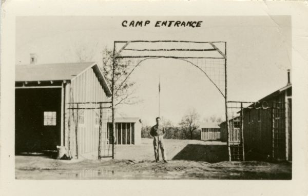 A man stands in the entrance archway to the Civilian Conservation Corps (CCC) Camp Petenwell.
