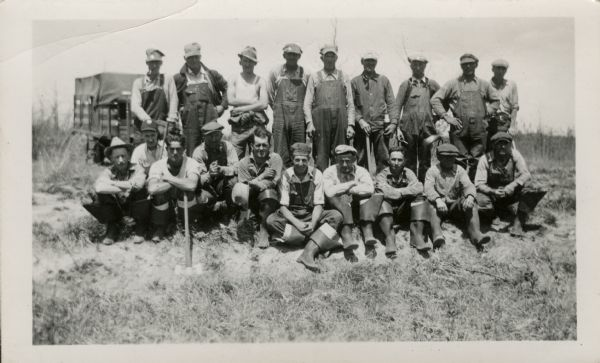 Group of men posing in two rows in a field. The men sitting and crouching in the front row are wearing folded down rubber boots. The men standing behind them are wearing overalls. There is a truck parked in the background.