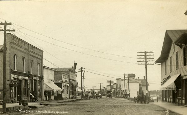 View down unpaved street towards many businesses: Carl Olson Shoe Store, Wakeman's Pharmacy, Jay Jennings, dentist, O.G.H. Parman, Badger Hardware, L.G. Bishop Meat Market, J.E. Daly Drug Store, J. Williams & Bros. Hardware, Carl Olson Shoe Store, a restaurant, the post office, and Jacob Gross General Store. There are multiple horse and wagon vehicles parked or rolling down the street. Men are standing, sitting and walking along the street. A unicycle is parked outside the general store.