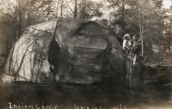 A Native American Ho-Chunk woman stands holding a baby outside a wigwam. Another child stands just in front of the woman, looking off to the right. The photograph has been annotated 'Indian Camp Necedah, Wis'.