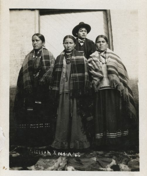 "Three women and a young man pose in front of the wood door of a brick building. The man stands behind the three woman, and is wearing a hat, suit coat and bow tie. He appears to be holding a cigar. They are traditionally dressed. The photograph is annotated ""Necedah Indians."""