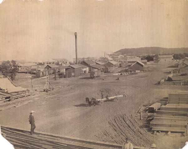 Elevated view of a lumber mill. Piles of milled wood are in the foreground and on the right, with more stacks in the far background behind numerous small buildings and a tall chimney. Working men are posed, one standing on a stack of wood on the left, and three men posing on a horse-drawn wagon. In the far background is a bluff.