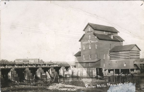 View across river of the Model Roller Mills, with the date 1884, with a railroad trestle is on the left. The mill wheel is turning.