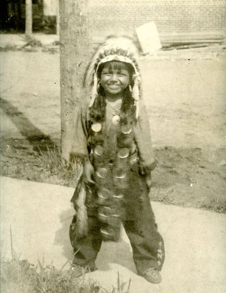 Portrait of Josh Sanford in Native American dress as a child. Sanford served in the Army Air Corps during WWII and is credited with being the only Native American pilot to serve in China. Sanford eventually reached the rank of Captain, won the Fly Cross Award, and took part in at least 74 combat missions. Sanford's mother was a member of the Winnebago Tribe while Sanford's father was a member of the Seneca Tribe.