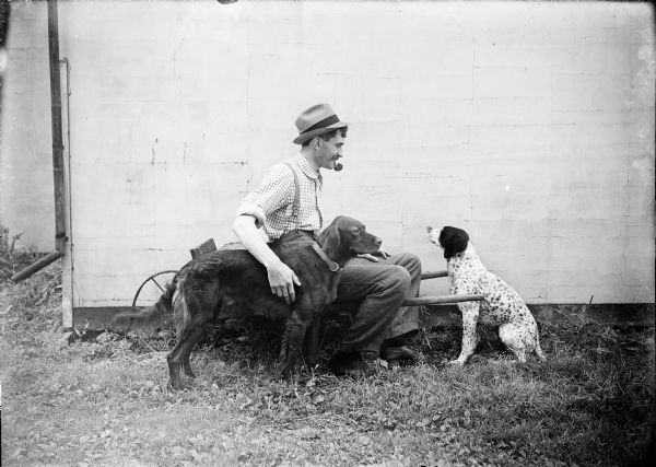 Outdoor portrait of Kent Wood, with a pipe in his mouth and sitting in a cart, posing with two dogs. All three are in profile. The side of a building is behind the group.