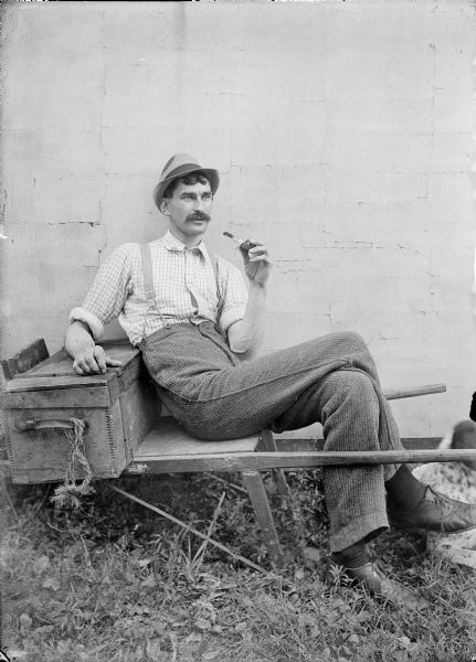 Outdoor portrait of Kent Wood sitting on a wooden wheelbarrow against a wall holding a pipe. He has his right arm resting on a wooden box. A dog (at the edge of the image at right) is lying at his feet.
