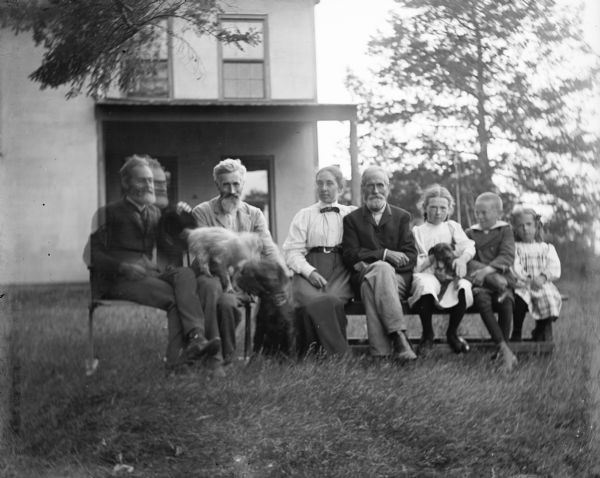 Outdoor group portrait of the Thwaites-Turvill family. Seven members of the family, and three dogs, are sitting on chairs and a bench in the front yard of their family home.