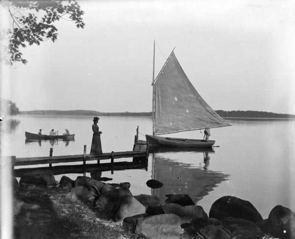 View from rocky shoreline of Turvill's new sailboat tied to a dock. A women is standing on the narrow wooden dock. A man is standing in the sailboat, with his face blocked by the full sail. On the left behind the dock are three people in a rowboat. The far shoreline is in the background.