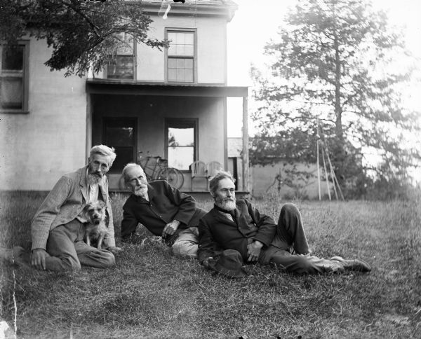 Outdoor group portrait of the Turvill brothers. All three men have beards. They are posing sitting on the ground in front of the family home. The man on the left is posing with a small dog.