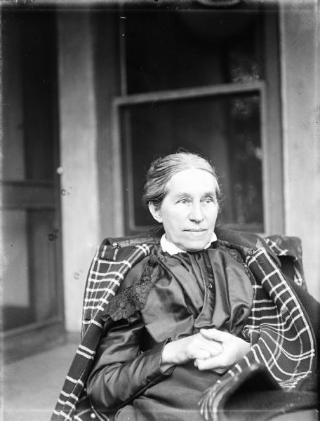 Outdoor portrait of Elizabeth Turvill Wood. She sitting in a chair in front of a window, with a coat draped over her shoulders and her hands clasped in her lap.
