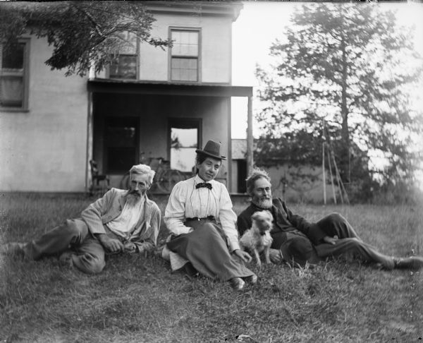 Outdoor group portrait of Thomas Turvill, William Turvill and Anna McConnell. They are sitting on the ground with a dog in front of the Turvill family home.