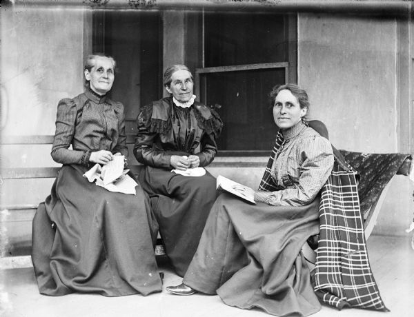 Outdoor family portrait of Mary Turvill McConnell, Elizabeth Turvill Wood, and Jessie Turvill Thwaites. They are sitting on a porch in front of windows with either hand sewing or a book in their laps. Jessie Thwaites has a coat draped over her right shoulder.