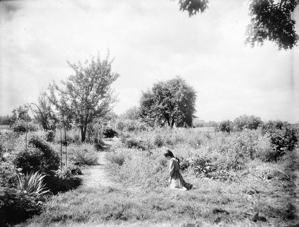 A unknown girl is kneeling in Turvill garden. She is wearing a dress and her hair is braided.  There is a path in the center and the gardens surround her. Trees are in the background.