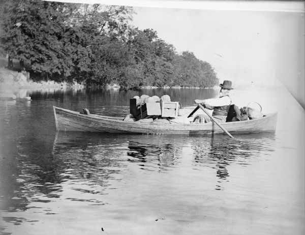 View over water towards William Turvill, rowing a boat loaded with farm produce in wooden crates and baskets. There is a tree-lined shoreline in the background.