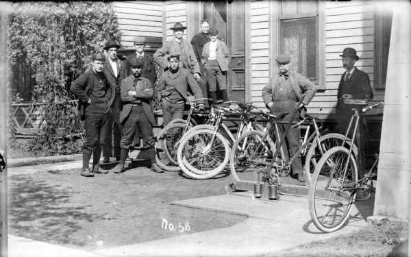 Group of men, and a young boy, standing in the small front yard of a house at a bicycling outing. A woman stands in an open doorway at the top of the steps. A man on the far right wears a suit and appears to be holding a cigar. Bicycles are leaning against a railing in front of the house. The men wear sweaters, jackets, hats, stockings, button-up shoes and knickerbockers. On top of a wood sidewalk in the yard is what appears to be a hand-pump with a long handle for putting air into bicycle tires.