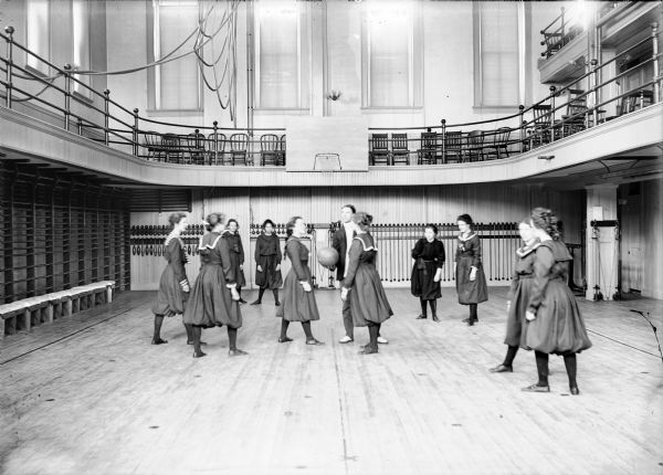 University of Wisconsin-Madison freshman women's basketball team in the gymnasium of Ladies Hall (now Chadbourne Hall). A man stands in the center holding a basketball for the tip-off.