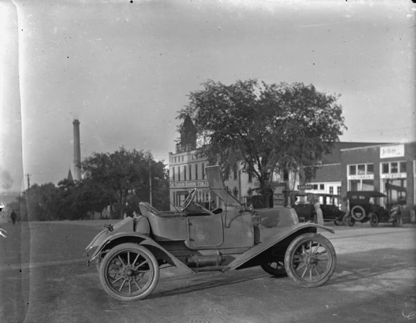 Right side view of a Ford Model T Runabout parked in the middle of East Washington Avenue. On the right side of the street in the background is the Fashion Boarding Stables, which is next door to the Palace Livery and a garage. In the far background is a smokestack.