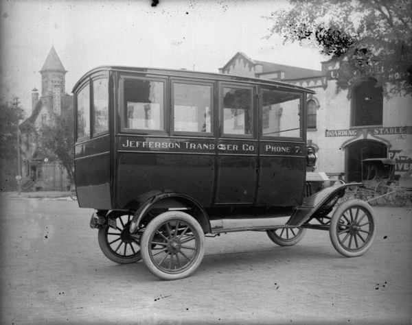 A bus for the Jefferson Transfer Company sits in front of the Schoelkopf Automobile dealership on East Washington Avenue. Behind the bus is a Boarding Stable and the Palace Livery. The bus is a 1915 Model T.