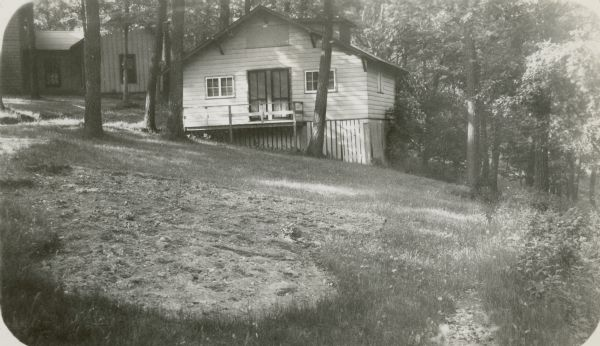 A simple wood frame cottage is built into the slope of the hill above Geneva Lake at Holiday Home Camp. A second building is seen in the background.