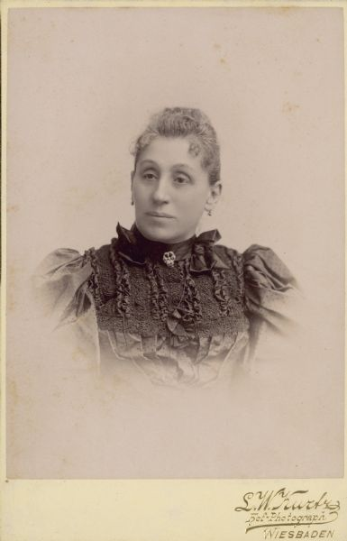 Quarter-length studio portrait of Maria Best Pabst (1842-1906). She is wearing a dress with leg of mutton sleeves and ornate embroidery. The daughter of successful Milwaukee brewer Phillip Best, Maria married Captain Frederick Pabst in 1862. Together they had ten children, only five of whom survived to adulthood. Pabst went into partnership with his father-in-law in 1863 and eventually owned what would become the Pabst Brewery.