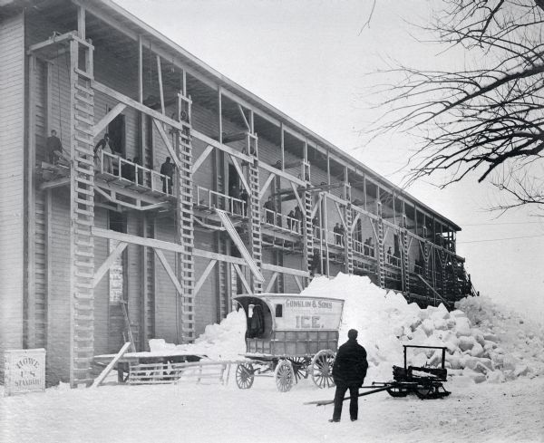 "Conklin Ice House on Lake Mendota. A man is standing in the snow-covered yard in the foreground near a sleigh, and a carriage with a sign painted on the side reading: ""Conklin & Sons Mendota Lake Ice."" Behind the carriage is a large pile of ice and snow. Men are working on the second floor gallery near wooden ladders and pulleys. On the far left is a box with painted with the words ""Howe U.S. Standard,"" probably a scale."