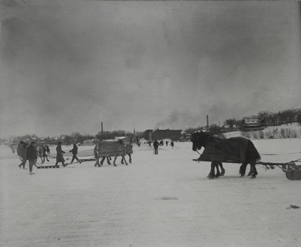 "View across ice towards a group of men, employees of the Conklin Ice House, which is in the distance, guiding horses pulling ice cutters. The horses are wearing blankets. In the foreground, grid lines are visible in the ice where the ice cutters have passed. The blanket on the horse in the center reads: ""Conklin and Sons N. 15."" In the background are a number of men carrying long poles. In the far background on the right is a water tower."