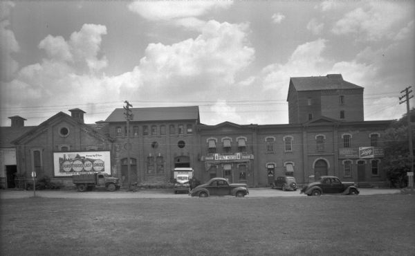 "View across lawn towards the Malt House at 1603 Sherman Avenue. To the right of the Malt House is the Cafferty Distributing Company, wholesalers for Schlitz beer — ""Just the Kiss of the Hops."" On the left is a large billboard for Kayser Motors Inc., with the slogan: ""Ford Trucks Last Longer."" A Cafferty delivery truck is parked below the billboard. Directly next to the Malt House is a Schlitz truck. Three automobiles are parked along the curbs. There is a sign for Lake Mendota on the far right."