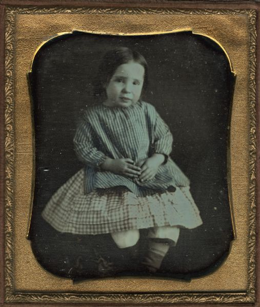 Sixth-plate daguerreotype of Ella or Irene Larkin as a child. Seated figure facing front with crossed ankles, wearing striped top and checked skirt. Hand-coloring on the cheeks and clothing. She was the daughter of Mr. and Mrs. B.F. Larkin.