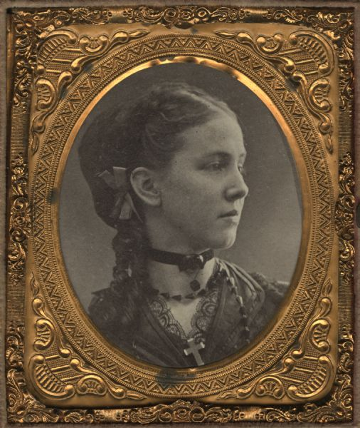 Cased albumen print of Irene Larkin, a school teacher. Bust figure facing right, wearing a choker, necklace, and a cross at her lace collar. She has a bow behind her right ear.