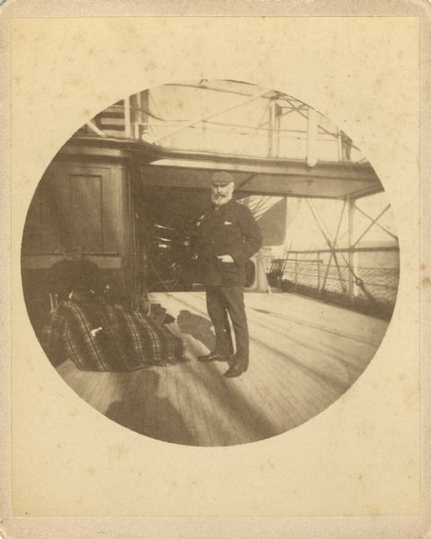 Frederick Layton standing on deck smoking a cigar while at sea in a Kodak #2 camera portrait by T.W. Ingersoll from St. Paul, Minnesota. The photographer's shadow is in the foreground. There is a second man sitting in a deck chair on the left, covered with a blanket.