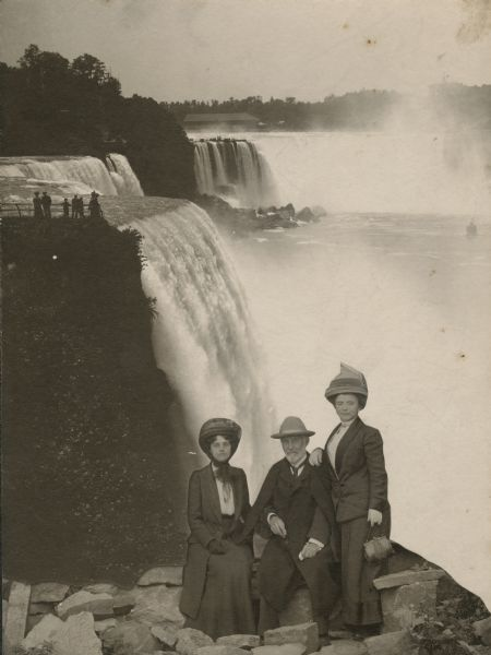 Frederick Layton posing in a studio shot with two women, one of whom is Laura Ackroyd. The backdrop is a photograph of Niagara Falls.