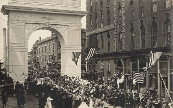 "Elevated view of a crowd lining the street near the ""Welcome Home"" Arch anticipating a parade of returning veterans. The facades of the buildings are decorated with flags."