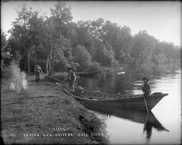 View along shoreline towards Indian log drivers, two in a bateau, and one man standing on the bank of the Chippewa River.