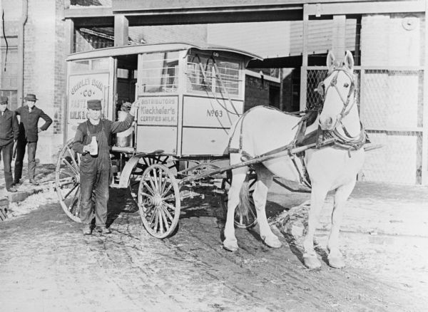A man holding a bottle of milk is standing and posing next to a horse-drawn Gridley Dairy milk wagon. Two other men are standing on the left near a brick building in the background.