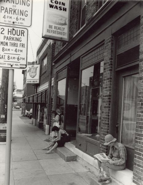 View down a sidewalk towards three people waiting outside of a coin laundromat on Williamson Street. Two women, one on steps of a doorway and another near a closed door, are sitting and reading newspapers. Another woman is standing and leaning against a window. Next door to the laundromat is Star Liquor.