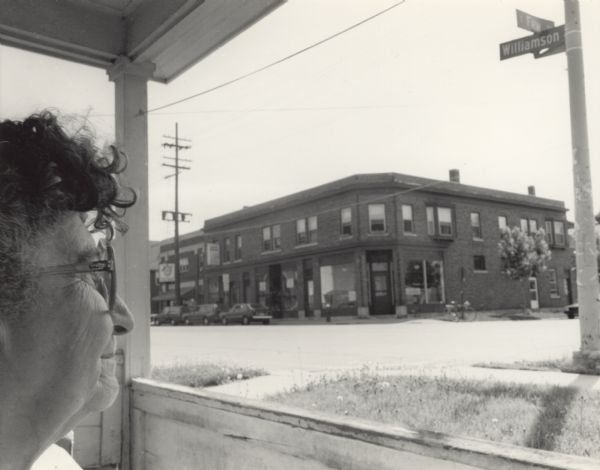 A profile view of the head of a woman, Suzy nee Elvira Dambry, sitting on a porch and looking across the street at a large brick building on the corner of Williamson and Few Street.