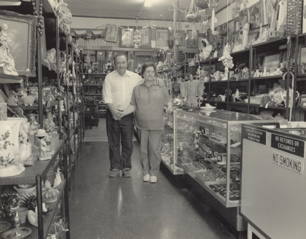"A couple, Doris and Preston Campbell, standing and posing in their store. Preston has his left arm around his wife's shoulders, and the two are holding hands. Doris is resting her right arm on a display case. The room is lined with shelves and cases, holding various objects such as wind chimes, cups, figurines, jewelry, and pictures. Their store is called the ""Pantry."""