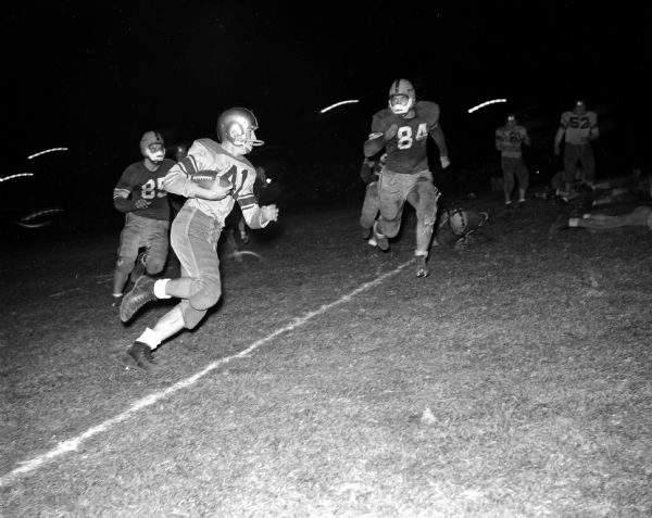 Madison West High School's Howard Mazur (41) carries the ball against Madison East during their football game. Madison East High School players include Ron Haisting (85) and Dave McCloskey (84).