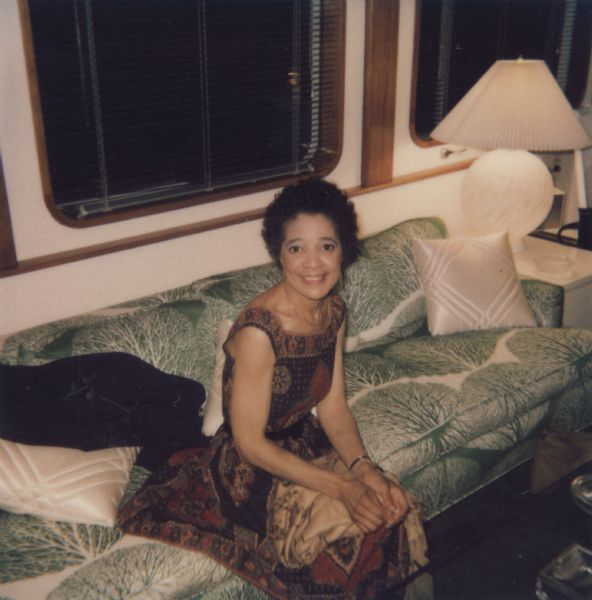 Vel Phillips, wearing a patterned dress and sitting on a green and white tree-patterned couch.