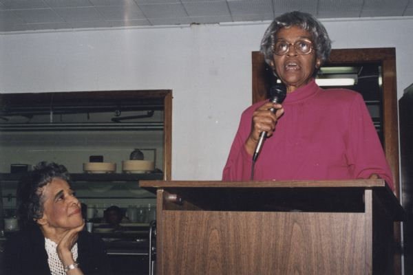 Vel Phillips sitting, on left, and looking on as Mother Naomi Scott speaks into a microphone at a podium at the Community Brainstorming Conference.