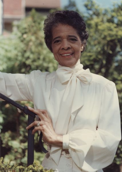 Waist-up portrait of Vel Phillips in a white blouse posing outdoors next to a railing.