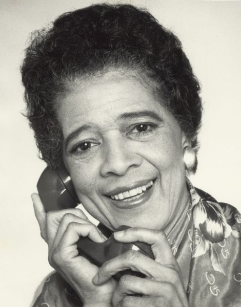 Head and shoulders portrait of Vel Phillips holding a telephone.