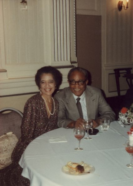 Vel Phillips wearing a floral patterned dress sitting at a table next to her husband, W. Dale Phillips, who is wearing a suit and eyeglasses.