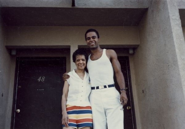 Vel Phillips wearing striped shorts standing next to her son, Dale Phillips. They are standing in front of a doorway.