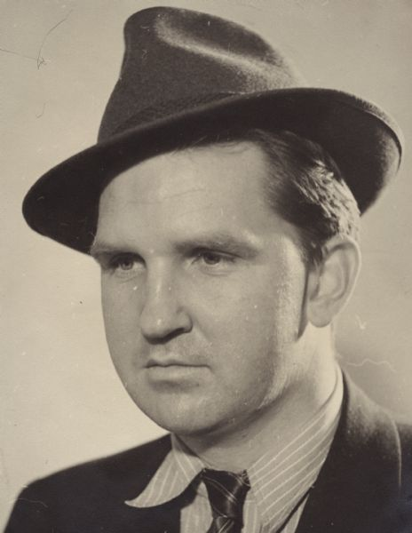 Head and shoulders portrait of Sid Boyum costumed as Spencer Tracy. He is wearing a hat, neck tie, and jacket.