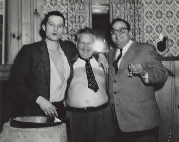 Group portrait of Sid Boyum (center) standing in between two of his friends. Sid is wearing a tie and pants, but no shirt.