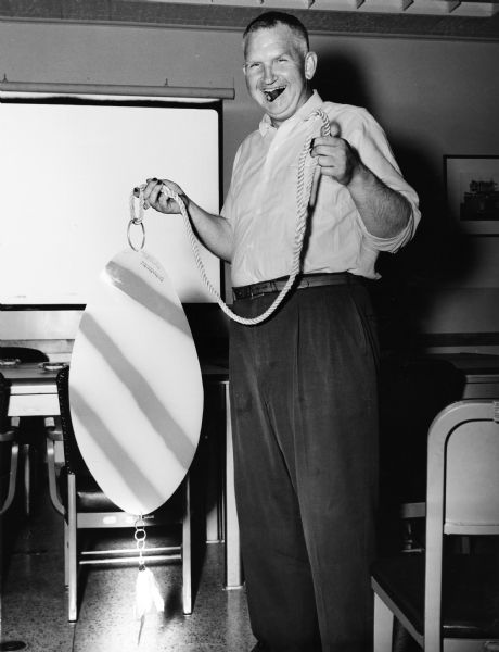 Portrait of Sid standing in a room holding an oversized fishing lure attached to a rope. Sid has a cigar in his mouth, and his fingernails are stained, probably with pyrogallol, a staining agent used in the development of film. Behind Sid are tables and chairs, and a screen on the back wall.