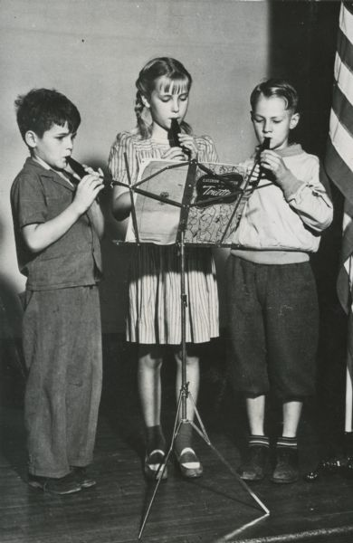 Steve, Sid Boyum's son, and two other children, playing the flutophones, standing together on a stage.
